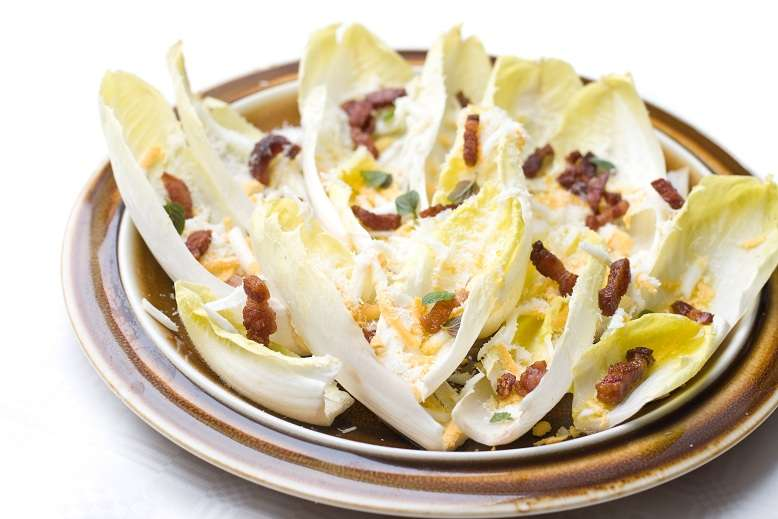 chicory salad with bacon, eggs and hard cheese