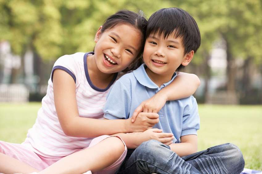 Portrait Of Chinese Boy And Girl Sitting In Park Together