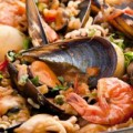 Seafood Paella with mussels, shrimps and calmari as closeup in a pan
