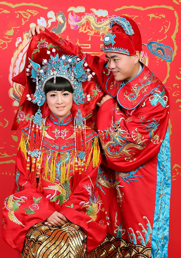 Chinese young couple dressed in traditional wedding suite in typical Chinese wedding ceremony
