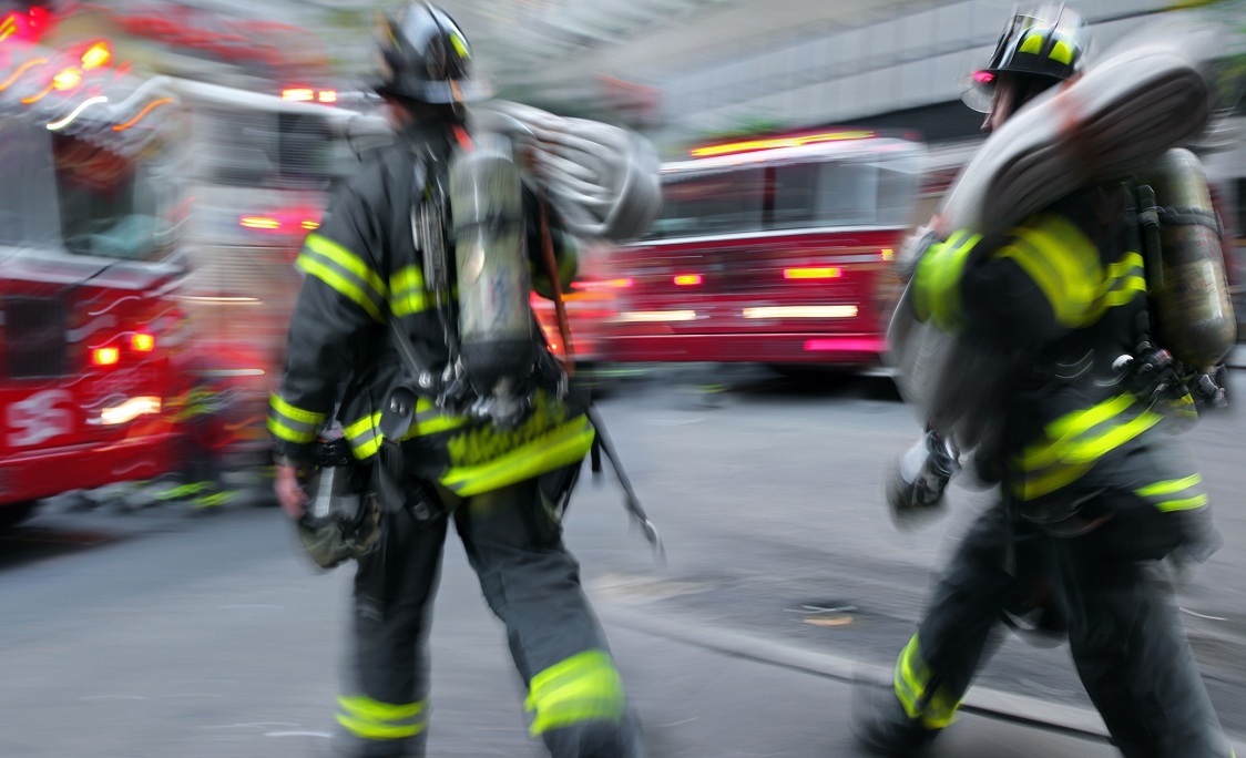 two firemen next to firetruck motion blur