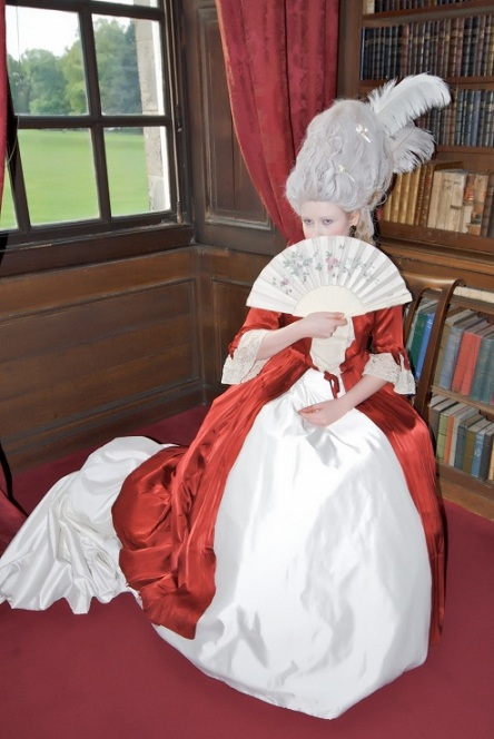Female dressed as Marie Antoinette sitting by window
