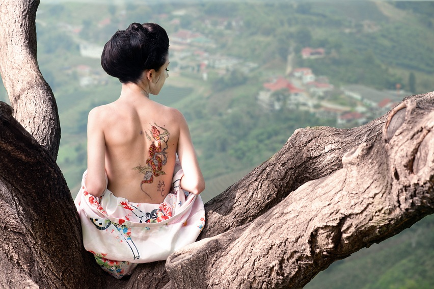 Woman with snake tattoo sitting on tree branch (Orig)